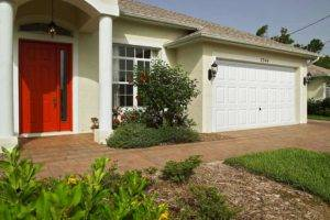 white garage door on a house with red front door