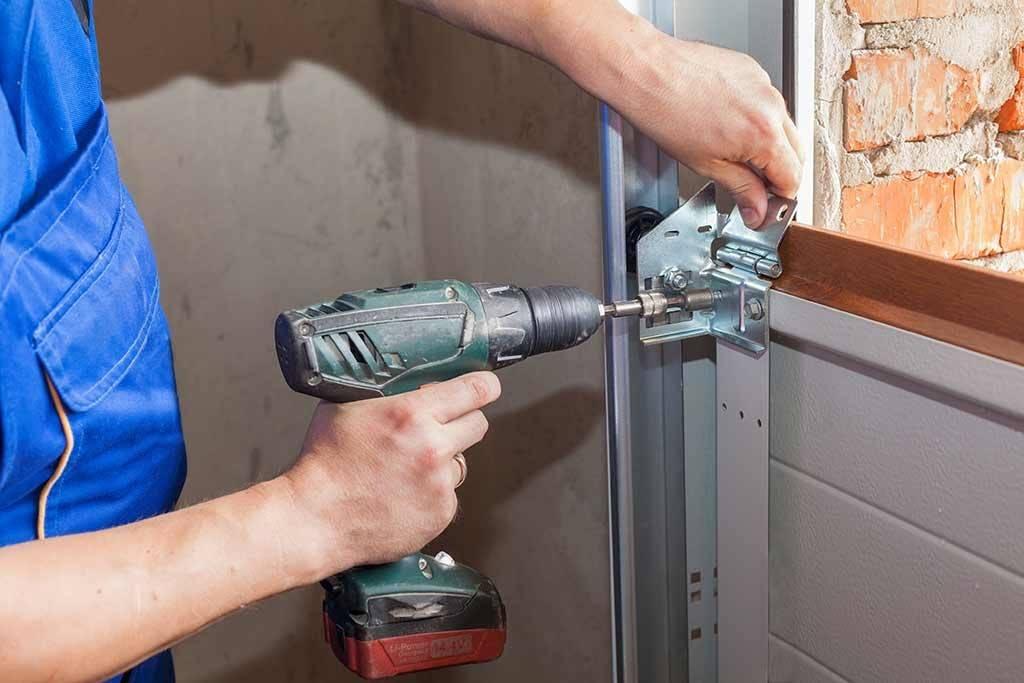man drilling bolt on garage door