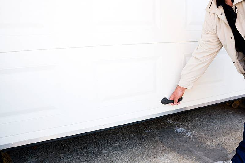 person opening white garage door from the bottom